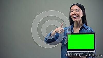 Усмехаясь женщина показывая большие пальцы руки-вверх держа зеленый ноутбук экрана, онлайн образование сток-видео