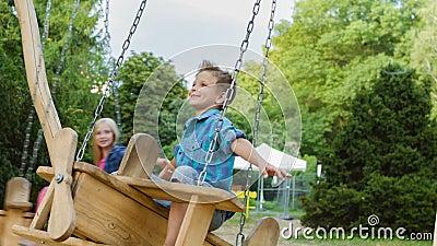 Усмехаясь мальчик и девушка имея потеху на спортивной площадке Дети играя outdoors в лете Подростки ехать на качании снаружи видеоматериал