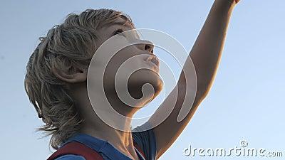 Усмехаясь ребенок смотря голубое небо видеоматериал