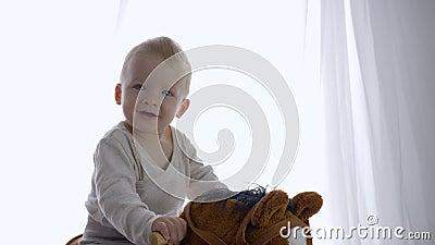 Утеха ребенка, жизнерадостное катание эмоции смака ребенка на игрушке equine в комнате видеоматериал
