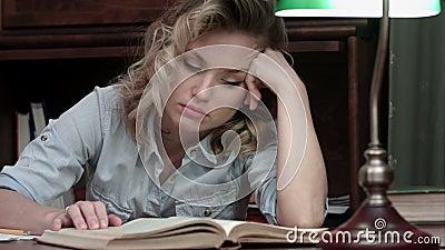 Утомленный падать молодой женщины уснувший над книгой пока сидящ на таблице после длинного рабочего дня видеоматериал