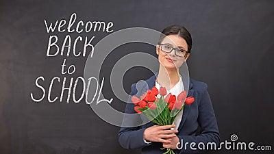 Учитель дамы усмехаясь и держа пук тюльпанов, гостеприимсво назад в написанную школу акции видеоматериалы