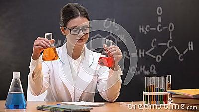Учитель химии сравнивая жидкости в склянках и показывая к камере, открытию сток-видео