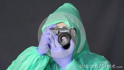 Фотограф с резиновыми перчатками, плащом и очками переворачивает фокус-кольцо камеры и начинает снимать сток-видео