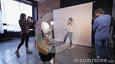 Фотомастерская, компания творческих фотографов фотографирует молодую модель во время обучения в студии стрельбы сток-видео