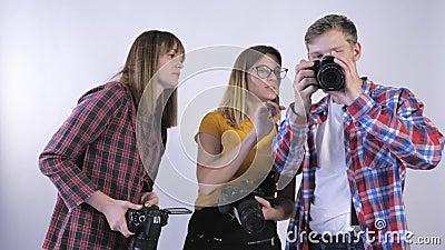 Фотошкола, компания молодых операторов с цифровыми фотоаппаратами в руках, обсуждающих фотографии в студии сток-видео