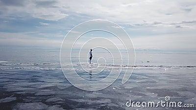 Футболист стоит в середине Lake Baikal Живописное Lake Baikal трескает голубые лоснистые ясные торошения льда видеоматериал