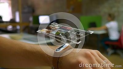 Футуристический прибор на руке человека, hologram, умном офисе дозора на заднем плане сток-видео
