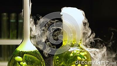 Химические жидкости в склянках кипя испускающ дым на темной предпосылке, извлекая видеоматериал