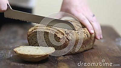 Хлебопек режа свеже испеченный хлебец домодельного органического хлеба рож sourdough с ножом хлеба сток-видео