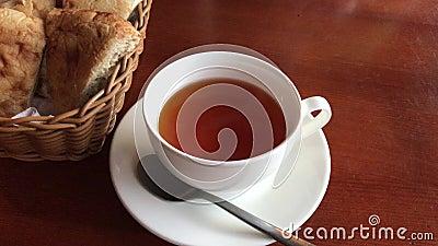Чашка стоек черного чая на коричневой таблице, рядом с корзиной отрезанного хлеба видеоматериал