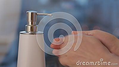 Человек, выливающий мыло из резервуара с насосом в руки сток-видео