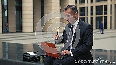 Человек в официально костюме работает на компьтер-книжке видеоматериал