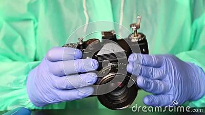 Человек в резиновых перчатках, в плащах и очках открывает крышку камеры для пленки Обслуживание фотографий сток-видео