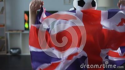 Человек держа флаг Великобритании, сторонника смотря футбольную игру на ТВ дома сток-видео