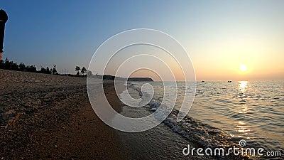 Человек идет вдоль берега Lake Baikal на заходе солнца видеоматериал