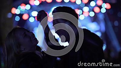Человек и женщина вися вне на музыкальном фестивале, наслаждаясь ночной жизнью, релаксация видеоматериал