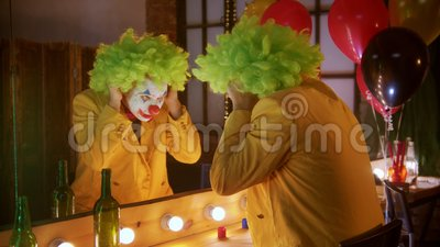 Человек-клоун надел зеленый парик и улыбнулся зеркалу сток-видео