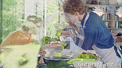 Человек надел перец на салат Молодые люди готовят еду или готовят еду на обед или ужин на домашней открытой кухне сток-видео