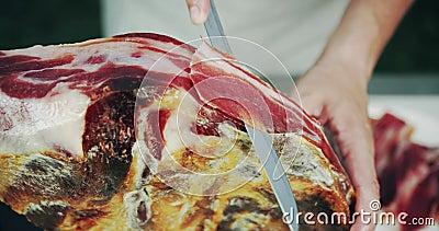 Человек отрезая ногу jamon, тип сух-вылеченной ветчины от Испании Конец-вверх снятый на красном цвете видеоматериал