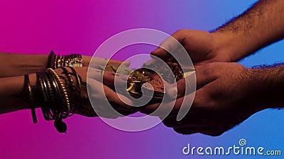 Человек передает плиту специй к индийской женщине с много браслетов и mehendi на ее руках, изолированную на яркой предпосылке сток-видео