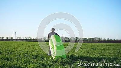 Человек пробует уловить ветер для того чтобы сделать раздувную кровать Зеленый цвет красивейший лужок акции видеоматериалы