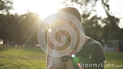 Человек сидит на траве в зеленом парке, игре с молодой маленькой собакой Предприниматель дразнит doggy, играет и обнимает Усмехат акции видеоматериалы