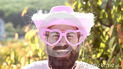 Человек эмоции со смешными солнечными очками пинка хипстера и шуточной розовой шляпой Бородатый сумасшедший человек смотря камеру видеоматериал