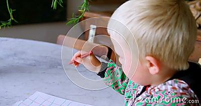 Чертеж мальчика с покрашенным crayon на бумаге дома 4k видеоматериал