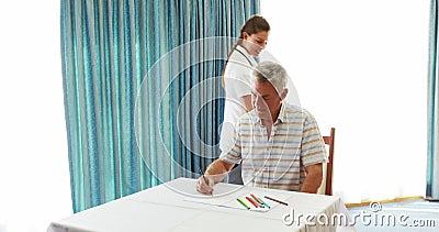 Чертеж старшего человека на бумаге помогая медсестрой сток-видео