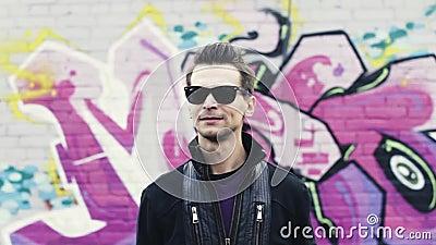 Человек в солнечных очках показывать, развевает голова в камере Тазобедренный хмель Граффити огораживают на предпосылке субкульту видеоматериал