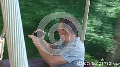 Человек закручивает на carousel и снимает видео на камере сток-видео