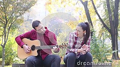 Человек играя гитару пока петь женщины сток-видео