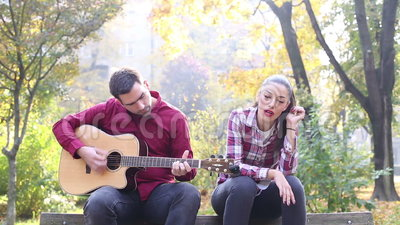 Человек играя гитару пока петь женщины видеоматериал