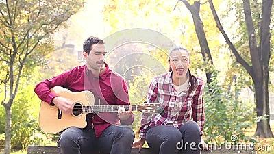 Человек играя гитару пока петь женщины акции видеоматериалы