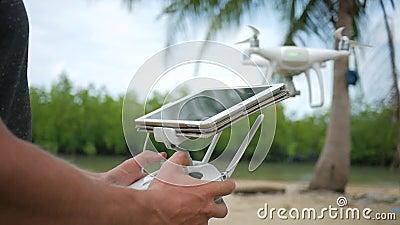 Человек контролирует Quadcopter летая через дистанционное управление с экраном устройства таблетки Полет практики трутня пилотный видеоматериал