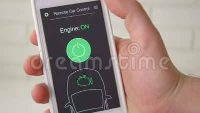 Человек удаленно начинает двигатель его автомобиля Дистанционное управление автомобиля используя интерфейс применения smartphone  видеоматериал