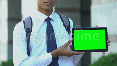 Школьник показывает планшетный планшет с зеленым экраном, рекламирует приложения библиотеки ebook сток-видео