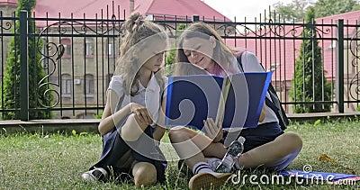Школьницы сидят на траве с книгами, тетрадями сток-видео
