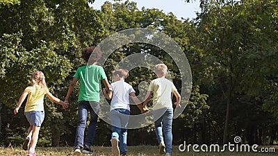 Школьные дети, держащиеся за руки в парке, отдыхающие в летние каникулы видеоматериал