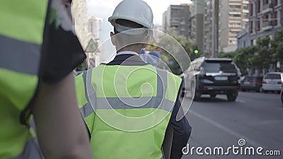 Шлем маленькие работник дороги или оборудование для обеспечения безопасности и конструктор контролера нося идя с неузнаваемым асс акции видеоматериалы
