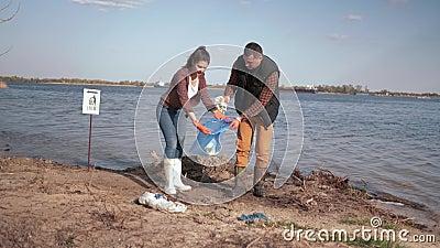 Экологичность, активисты волонтеров пар очищает вверх загрязнятьый обваловку реки от пластиковой погани и собранный в сумке отбро видеоматериал