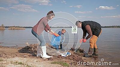 Экологичность природы заботы, волонтеры семьи с маленьким сыном очищая вверх по пластмассе и погань полиэтилена на грязном портов видеоматериал