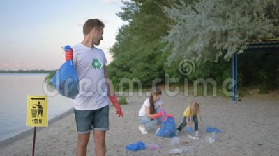 Экологичность природы заботы, портрет усмехаясь добровольного парня в резиновых перчатках с сумкой отброса около знака указателя  сток-видео
