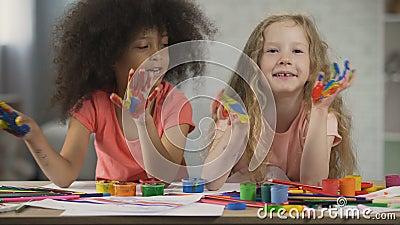 Ягнит клуб искусства Multiracial дети развевая покрашенные ладони и поя, детство сток-видео