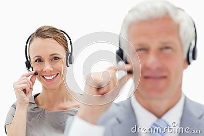 一名微笑的妇女的特写镜头谈话在与白色h的背景中