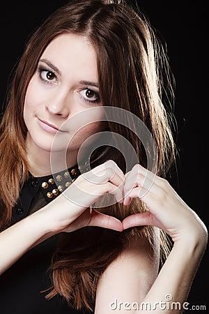 做心脏形状爱标志用手的青少年的女孩