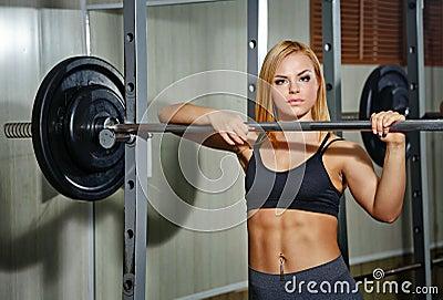 做与杠铃的女孩锻炼在健身房