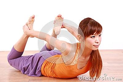 做瑜伽青蛙姿势的年轻日本妇女