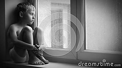 一个哀伤的男孩的黑白英尺长度坐窗台在暴雨期间,无法离开公寓 影视素材